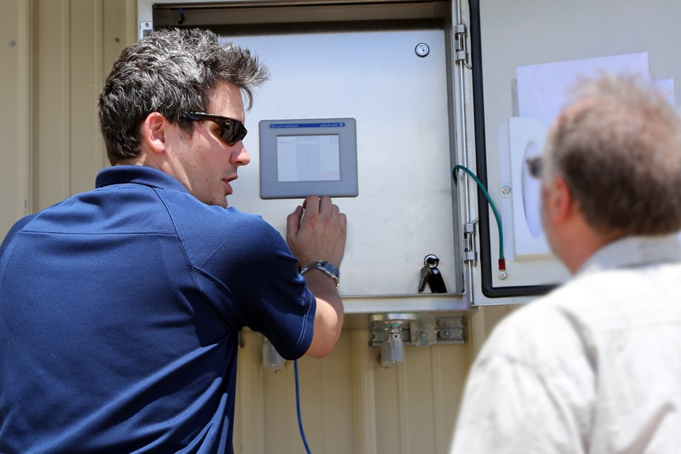 An EleMech engineer on field service trains a client on the use of a new station.