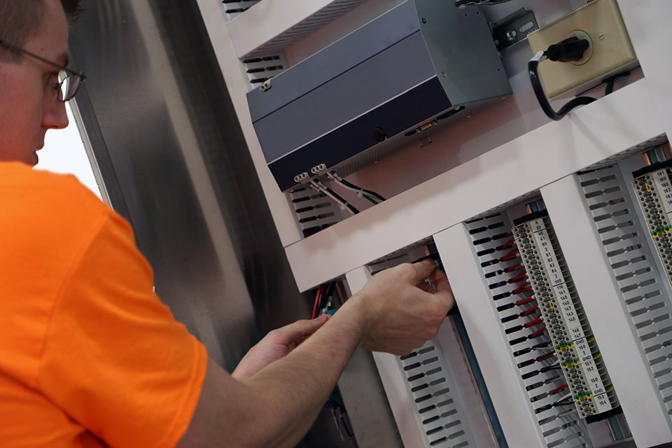 An EleMech employee testing wire connections in our modern and clean facility.